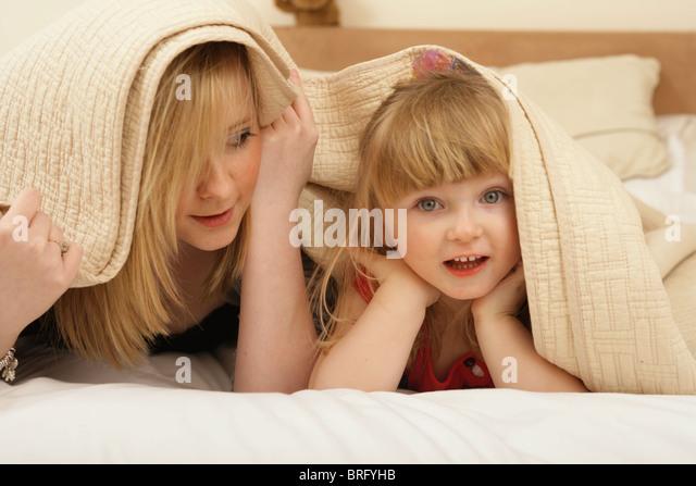 Zwei Schwestern unter Bettwäsche zusammen zu spielen. Stockbild
