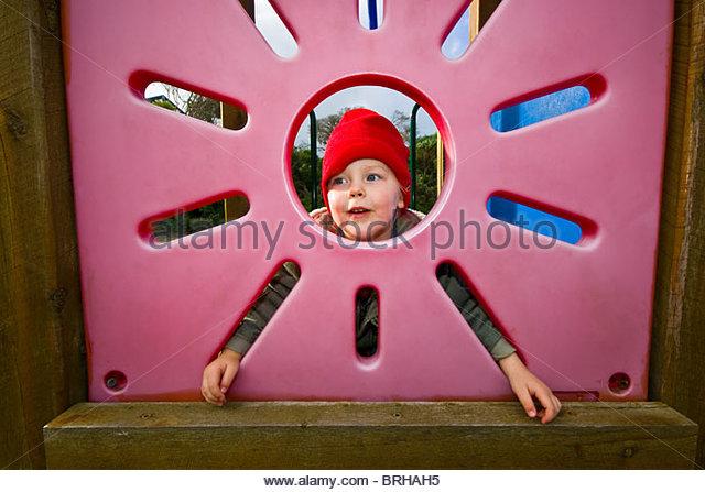 Ein kleiner Junge blickt durch ein Sonne-förmige Fenster in einem Spielplatz-Haus. Stockbild