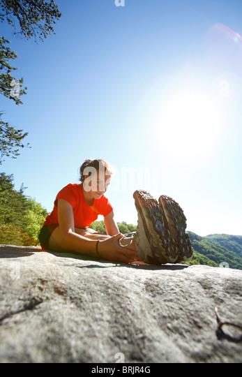 Frau erstreckt sich auf einem Berggipfel vor Trailrunning in einem üppig grünen Wald. Stockbild
