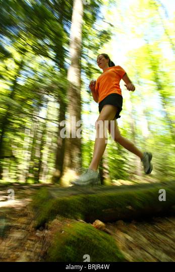 Trailrunning-Frau in einem üppig grünen Wald Stockbild