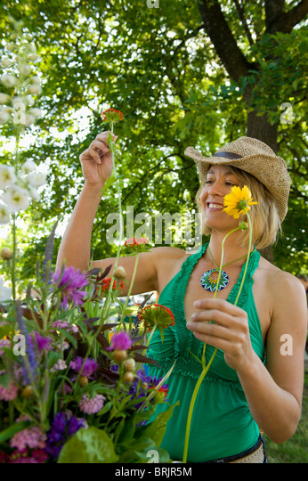 Eine junge Frau nimmt aus Blumen auf einem Bauernmarkt. Stockbild