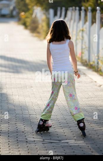 Ein junges Mädchen ist Inline-Skating in einer Gasse mit einem Zaun im Hintergrund. Stockbild