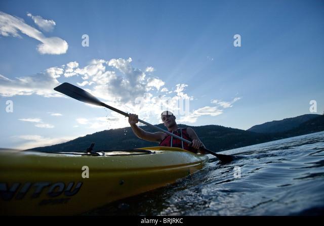 Junger Mann Paddel gelb Kajak auf See. Stockbild