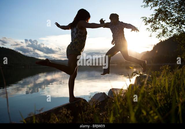 Zwei junge Erwachsene balancieren auf Felsen bei Sonnenuntergang am See. Stockbild