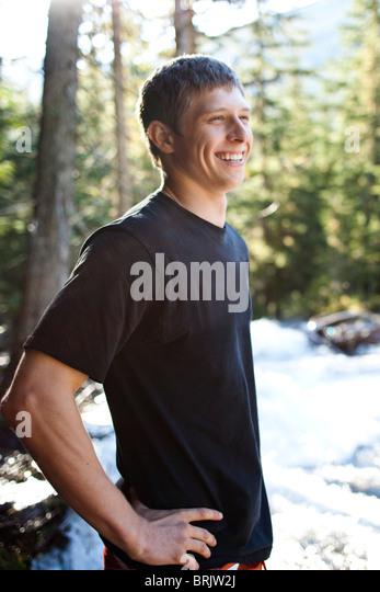 Ein junger Mann lächelt stehen neben einem reißenden Fluss in Idaho. Stockbild