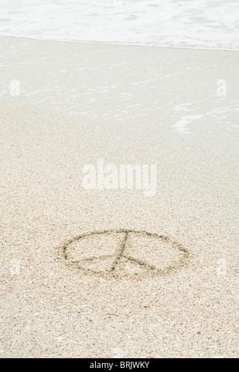 Peace-Zeichen im Sand am Strand gezogen Stockbild