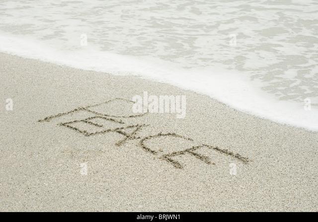 "Das Wort ""Frieden"" in den Sand am Strand geschrieben Stockbild"