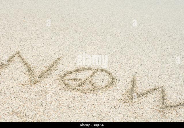 """Das Wort """"jetzt"""" geschrieben mit einem Peace-Zeichen im Sand (Frieden) Stockbild"""