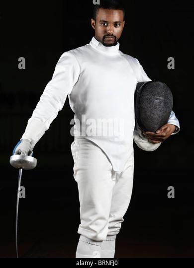 Porträt von ein Fechter Fechten Uniform trägt und hält ein Degen und eine Maske auf schwarzem Hintergrund Stockbild