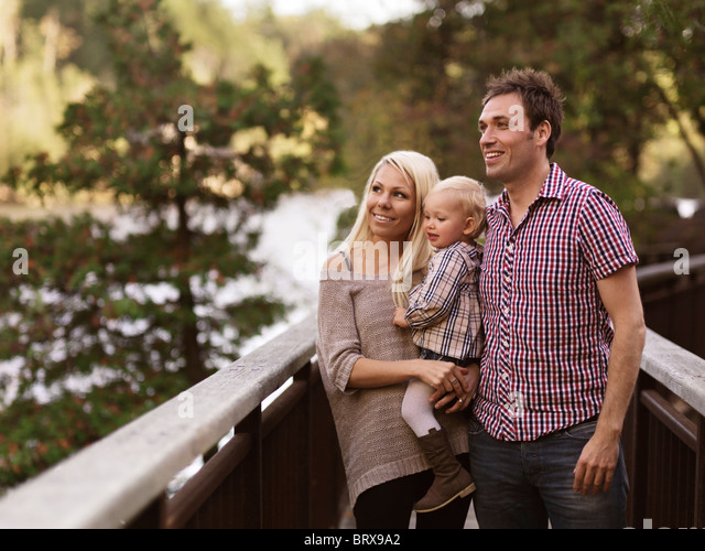 Glücklich lächelnde junge Eltern und ein zwei Jahre altes Mädchen, die die Natur genießen Blick Stockbild