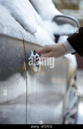 Entsperren einer gefrorenen Autotür Stockbild