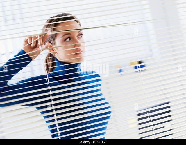 Frau auf der Suche durch Jalousien Stockbild