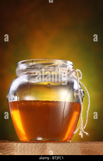 Topf mit Honig auf einem Holztisch. Stockbild