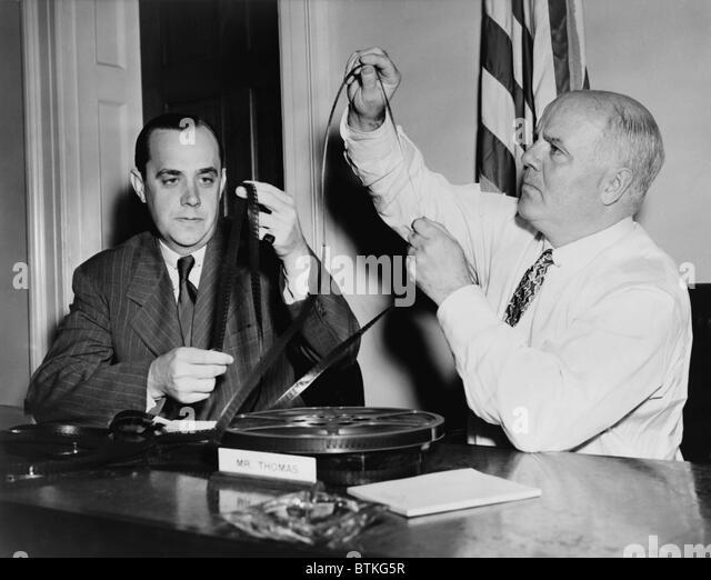 J. Parnell Thomas, Vorsitzender des Komitees für unamerikanische Umtriebe, (rechts), untersuchen Filme während Stockbild