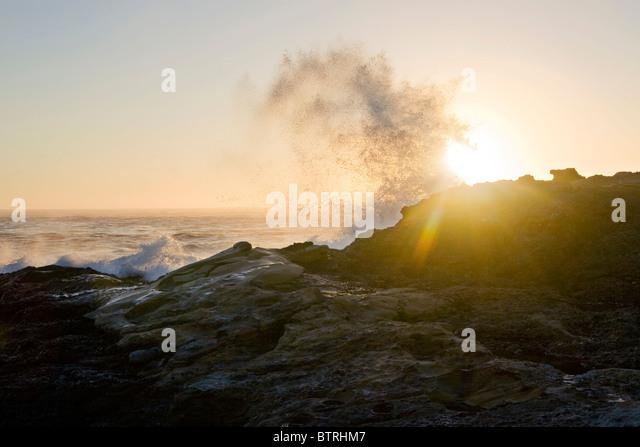 Eine große Welle stürzt über Felsen entlang der kalifornischen Küste bei Sonnenuntergang. Stockbild