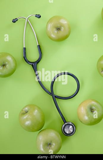 Stethoskop mit grünen Äpfeln Stockbild