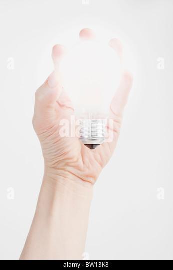 Hand hält eine leuchtende Glühbirne Stockbild