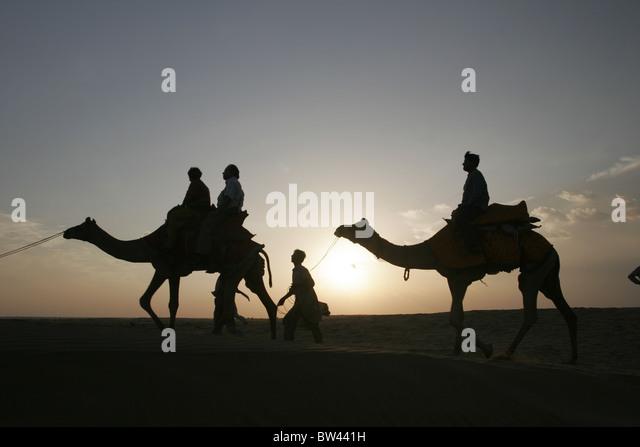 Touristen genießen einen Kamelritt am Sam, Jaisalmer, Rajasthan, Indien. Stockbild