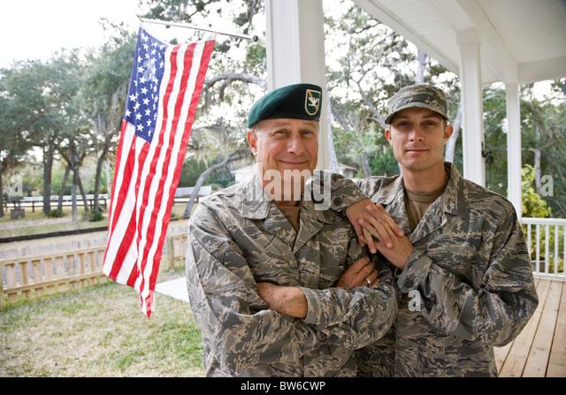 Vater und Sohn in militärischen Uniformen durch amerikanische Flagge Stockbild
