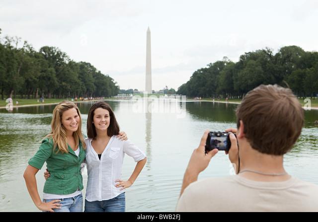 Junger Mann nehmen Foto von Freunden am Washington monument Stockbild