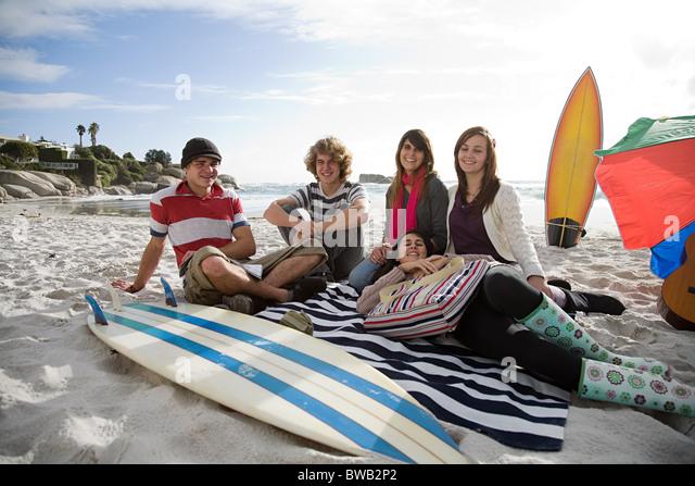 Freunde am Strand mit Surfbrett Stockbild
