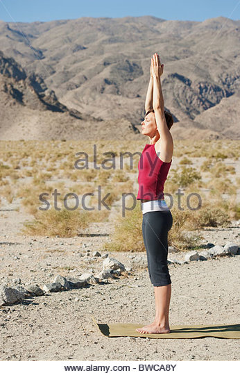 USA, Kalifornien, La Quinta, Frau stehend in Yoga-Baum-Pose in Wüstenlandschaft Stockbild