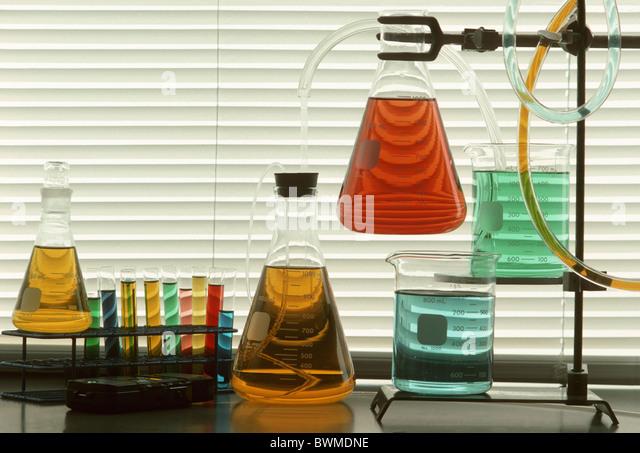 Wissenschaftliche Glaswaren und Rohre gefüllt mit farbigen Flüssigkeiten gegen Fenster-Vorhänge Stockbild