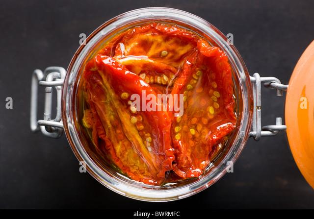 Ein Glas gefüllt mit Sun-Dried Tomaten und Olivenöl auf einem schwarzen Hintergrund. Stockbild