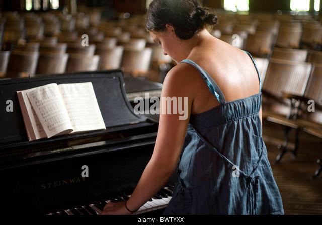 junge Frau spielt Klavier in einem alten Theater Stockbild