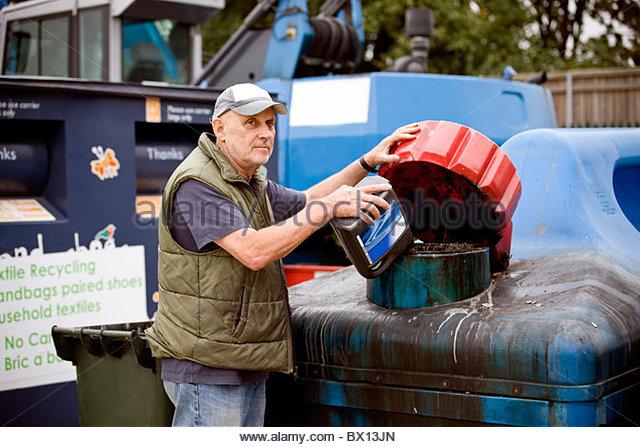 Ein älterer Mann goß Öl in einen recycling-container Stockbild