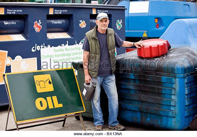 Ein senior Mann stand neben einem recycling Behälter für Öl Stockbild