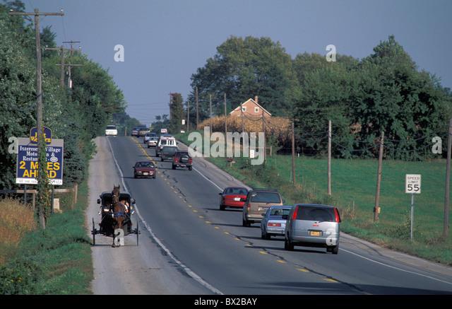alten altmodischen Amish Trainer Pferd Trainer Pferd Straße Pkw Autos Kontrast Opposition kontrastiert Widersprüche Stockbild