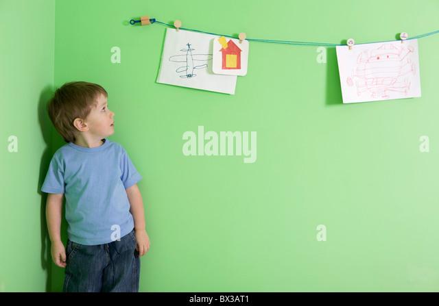 kleiner Junge betrachtet man Zeichnungen an der Wand hängen Stockbild