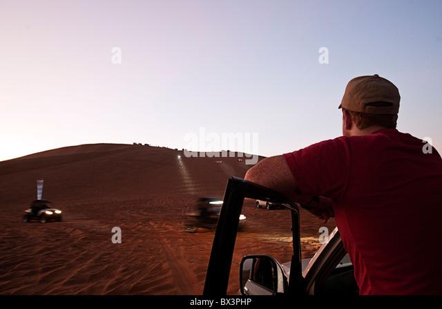 Mann beobachtet 4x4s auf den großen roten Sanddüne in Dubai, Vereinigte Arabische Emirate Stockbild