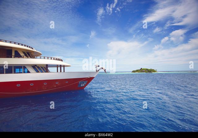 Junge Menschen springen vom Boot ins Meer, Malediven, Indischer Ozean, Asien Stockbild
