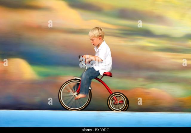 Kleiner Junge Reiten Dreirad gegen bunte Himmel mit Wolken Stockbild