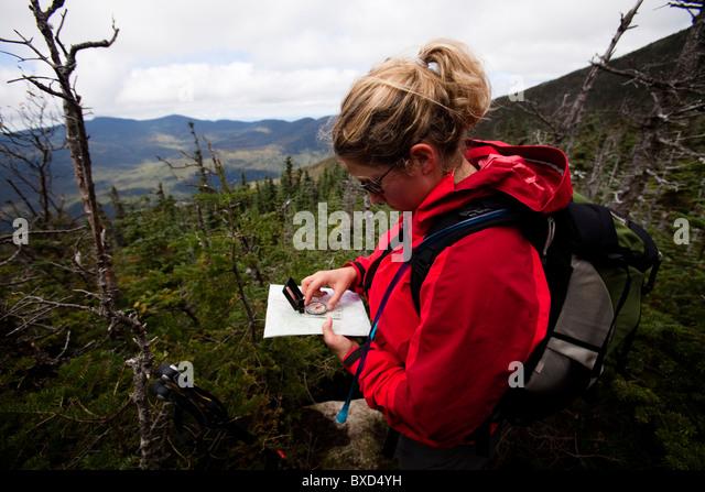Eine weibliche Wanderer prüft ihre Position mithilfe einer Karte und Kompass. Stockbild