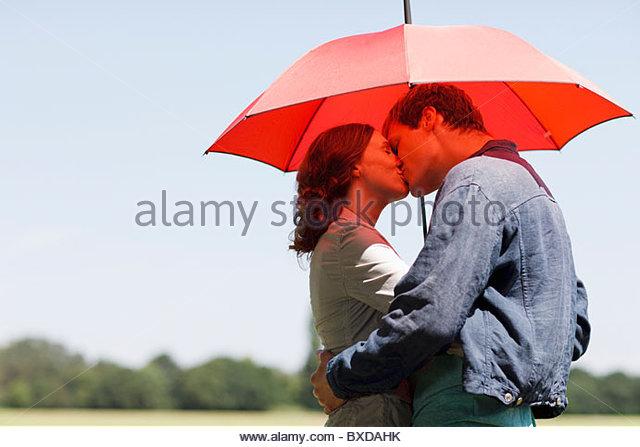 Paar küssen unter roten Regenschirm Stockbild