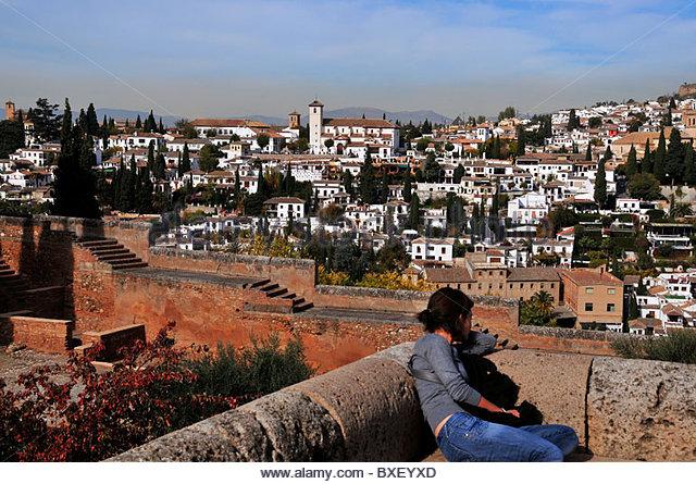Eine junge Frau sitzt an den Wänden der Alhambra und befasst sich mit der Altstadt von El Albaicin auf dem Stockbild
