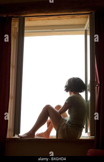 Frau aus dem Fenster schauen Stockbild