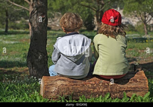 Zwei kleine Freunde sitzen auf einem Baumstamm im Wald. Stockbild