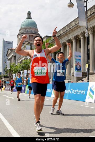 Läufer bei der Singapur-Marathon 2010, Supreme Court und Rathaus im Hintergrund. Stockbild
