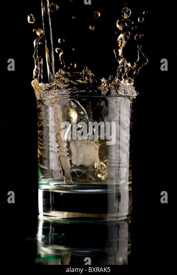 Glas Whisky auf einem schwarzen Hintergrund. Whisky-Spritzer in ein Glas. Whisky mit Eis. Stockbild