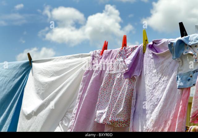 Kinderbekleidung und Bettwäsche haben aufgehängt wurden zum Trocknen auf einer Wäscheleine vor einem Stockbild