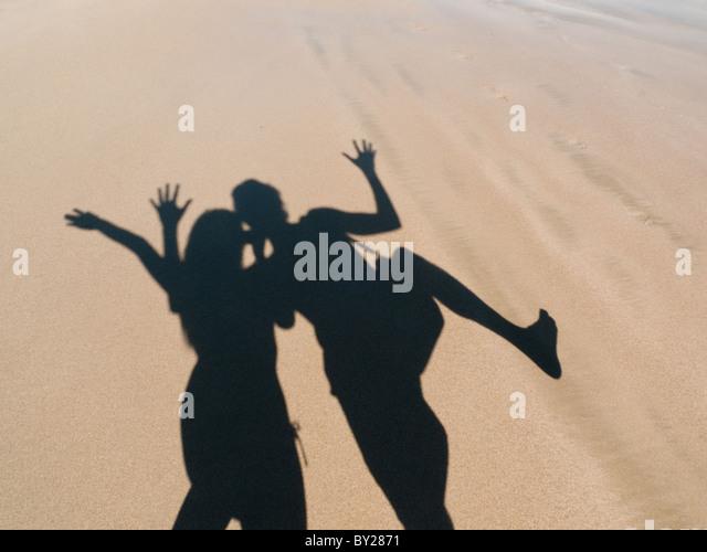 junges Paar mit Schatten auf Sand spielen Stockbild