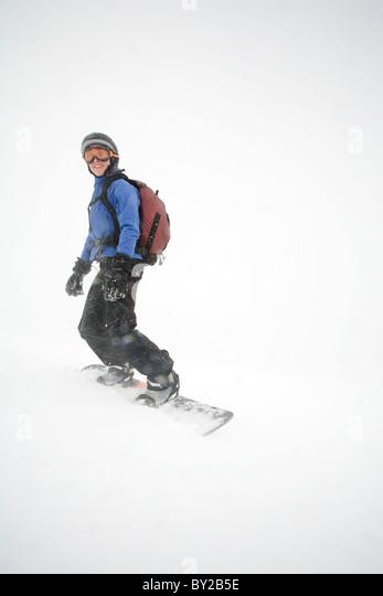 Snowboarder junge Frau posiert für die Kamera bei stürmischem Wetter auf Mount Hood, Oregon. Stockbild