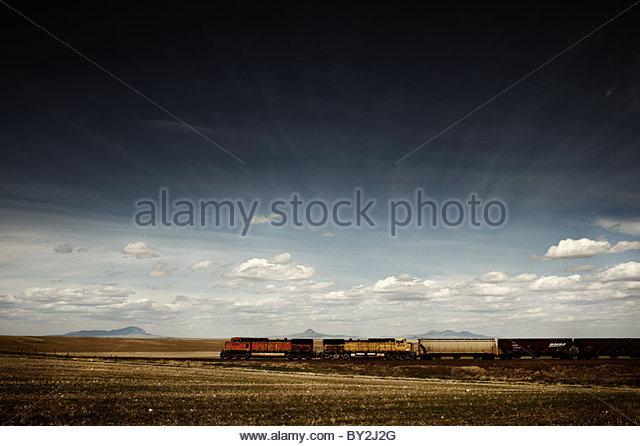 Ein Zug rollt durch die amerikanische Prärie südlich von Sweetgrass Hills in Montana. Stockbild