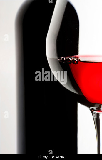 Stilleben mit Flasche und Glas Rotwein auf weißem Hintergrund. Stockbild