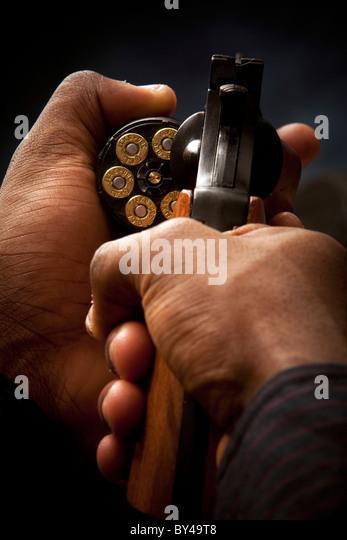 Junge schwarze männliche Model posiert mit einer Pistole Stockbild
