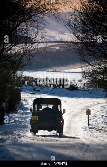 Ein Landrover fahren entlang einer Schnees bedeckt 'B' Landstraße im ländlichen Norden Northumberland. Stockbild